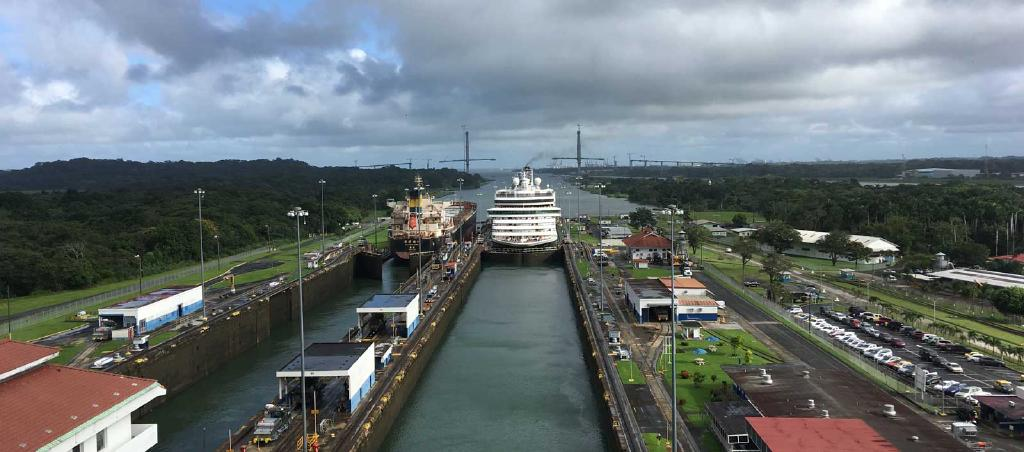 A look back at the Panama Canal. A long blue channel of water bordered by grass and low buildings. A Cruise ship is inside the canal, taking up the full width of the channel.