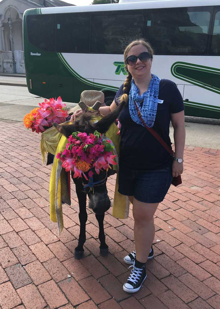 Cheri stands next to a donkey. The donkey wears a wreath of flowers. A tour bus is in the background.