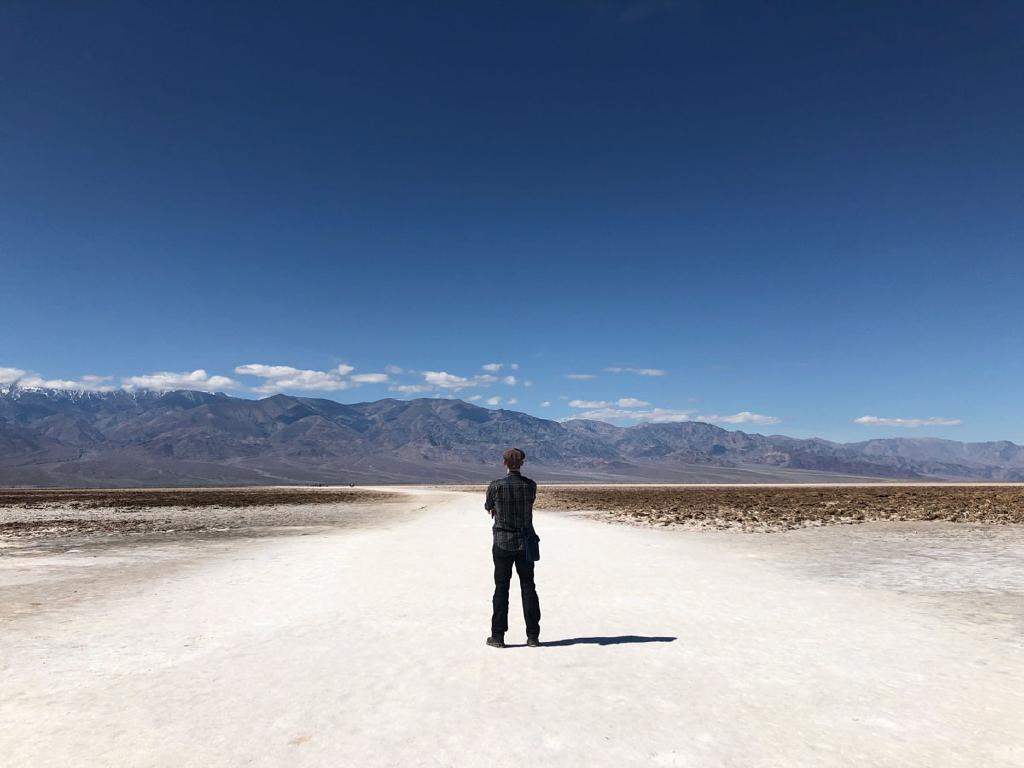 Patrick stands on a white path made of salt looking at distant mountains.