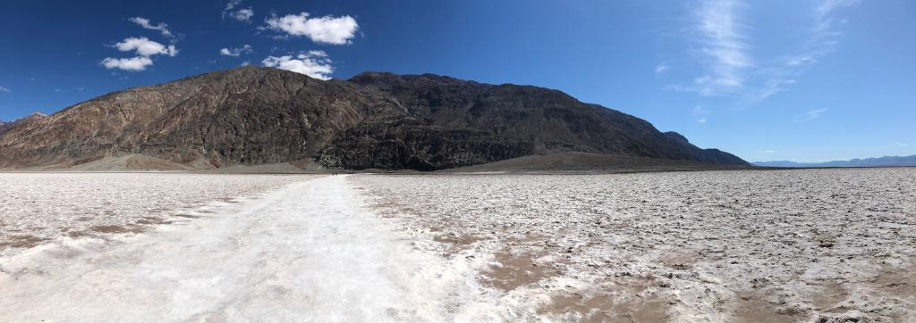 A panorama of a brown rumply mountain rising up behind a flat plain of white salt and brown earth