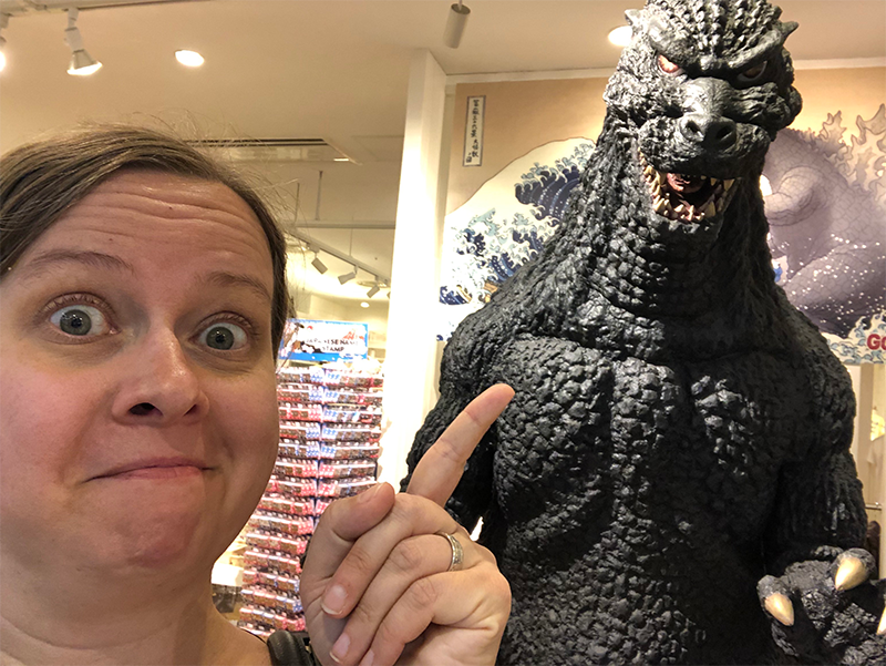 Cheri points at a Godzilla statue while making a fake-scared face.