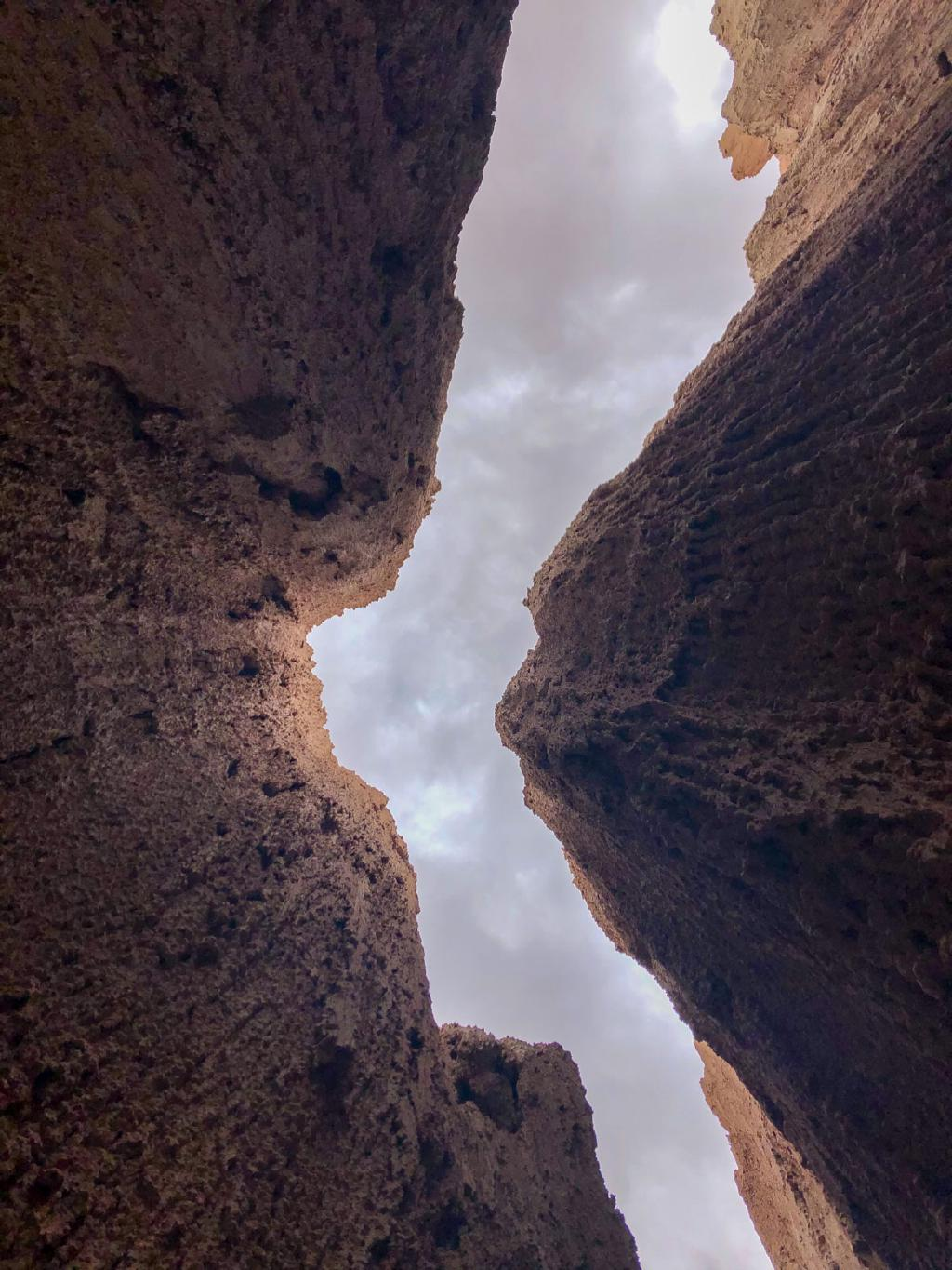 The camera looks straight up. A bent strip of sky is visible through the narrow gorge.