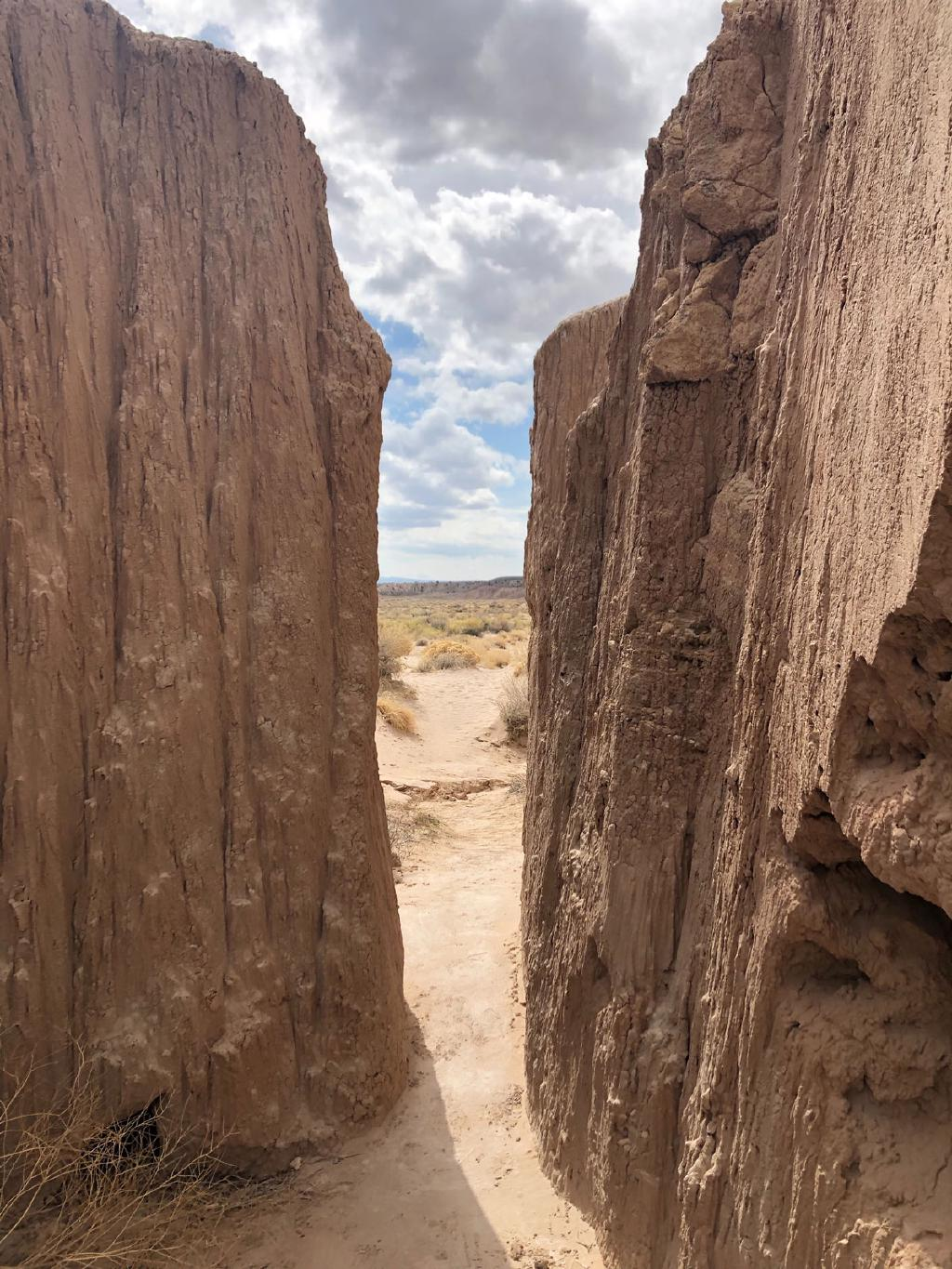 The camera peers through a gap between two red-stone walls to see a desert landscape beyond.