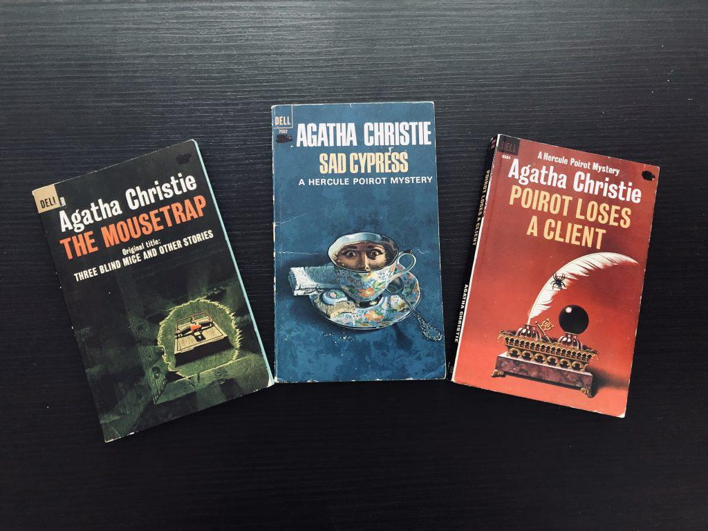 Three old-fashioned paperback novels with colorful covers on a wooden table. The books are: Poirot Loses a Client, Sad Cypress, and The Mousetrap.